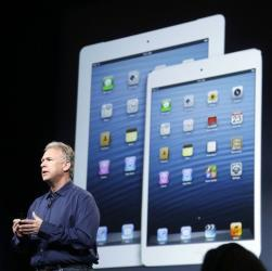 Phil Schiller, Apple's senior vice president of worldwide product marketing, speaks in front of an image of the 4th generation iPad, at left, and the iPad mini in San Jose, Calif., Oct.  23, 2012.
