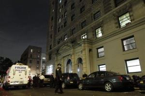A police crime scene vehicle is parked in front of the luxury Manhattan apartment building where the slayings took place.