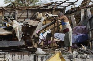 Resident Antonio Garces tries to recover his belongings from his house destroyed by Hurricane Sandy in Aguacate, Cuba, Thursday Oct. 25, 2012.
