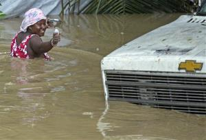 A resident of Leogane, Haiti, makes her way to her home as the water level continues to rise Friday.