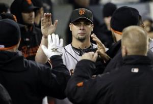 San Francisco Giants starting pitcher Ryan Vogelsong is congratulated in the dugout after leaving the game during the sixth inning.