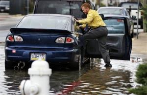 Cody Billotte walks through the high water as he loads his car to go to work as Hurricane Sandy bears down on the East Coast, Sunday, Oct. 28, 2012, in Ocean City, Md.