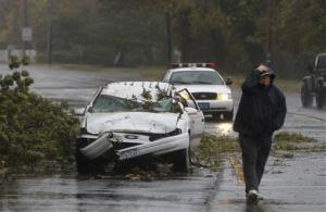 A car crushed by a fallen tree sits along Montauk Highway as Hurricane Sandy approaches, Monday, Oct. 29, 2012, in Bay Shore, NY.