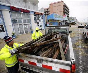 Michael Brown, left, and Enos Jones, with Ocean City, fill a truck with debris as they clean the boardwalk after the effects of Hurricane Sandy, Oct. 30, 2012, in Ocean City, Md.