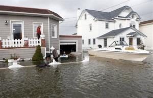 A boat floats in the driveway of a home in the aftermath of superstorm Sandy Tuesday in Lindenhurst, N.Y.