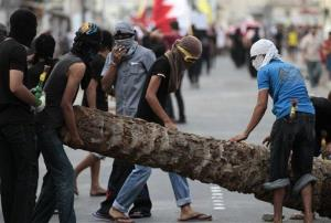 Anti-government protesters remove a palm tree trunk being used as a roadblock in Malkiya, Bahrain, to allow the passing of a march calling for freedom for political prisoners.