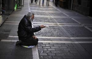 A man begs for alms in a street, in Pamplona, northern Spain, Tuesday, Oct. 30, 2012. Spain's National Statistics Institute says Tuesday that the country's economy contracted 0.3 percent in the third quarter from the previous three month period. Spain is in a double-dip recession and has a 25...