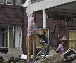 Marcus Konner, 22, boards his home in the aftermath of a storm surge from Hurricane Sandy, Tuesday, Oct. 30, 2012, in Coney Island's Sea Gate community in New York.