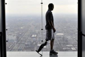 In this Oct. 25, 2012 photo, Zac Vawter, fitted with an experimental bionic leg, is silhouetted on the Ledge at the Willis Tower in Chicago. Vawter is training for the world's tallest stair-climbing event where he'll attempt to climb 103 flights to the top of theWillis Tower using the new...