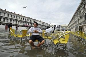 A tourist sits outside a cafe in flooded St. Mark's Square in Venice.