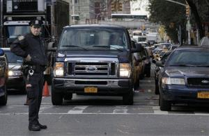 A New York City Police officer manages a line of drivers waiting for gasoline, in New York, Friday, Nov. 2, 2012.