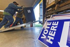 A delivery driver pushes a vote-counting scanner into a truck at the Pulaski County Election Commission warehouse in Little Rock, Ark.