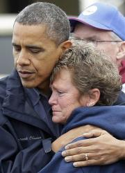 President Barack Obama, left, embraces Donna Vanzant, right, during a tour of a neighborhood effected by superstorm Sandy, Wednesday, Oct. 31, 2012 in Brigantine, NJ.