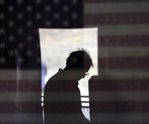 Hal Pigg is reflected in an image of a flag, as he casts his vote on Election Day, Tuesday, Nov. 6, 2012, in Jamul, Calif.