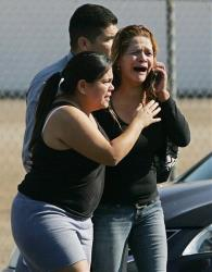 An unidentified woman cries as she's rushed into a car after learning of a workplace shooting in Fresno, Calif.