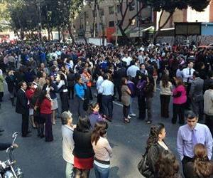 People who work in office buildings along El Paseo de la Reforma stand outside after evacuating their offices due to an earthquake in Mexico City, Wednesday, Nov. 7, 2012.