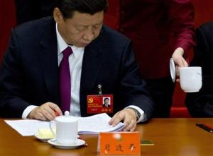 An attendant serves tea while Chinese Vice President Xi Jinping attends the opening session of 18th Communist Party Congress at the Great Hall of the People in Beijing, China,