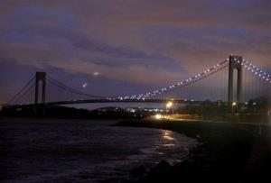 The half of the Verrazano Narrows Bridge attached to Brooklyn is lit while the half attached to Staten Island is dark in New York, Friday, Nov. 2, 2012.