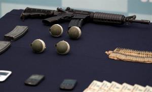Confiscated money, grenades, and guns are displayed during a media presentation of another alleged leader in the Zetas cartel, Ivan Velazquez Caballero, in Mexico City,Thursday, Sept. 27, 2012.