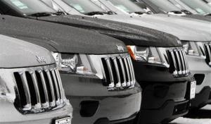 In this Jan. 31, 2012 photo, a row of 2012 Jeep Grand Cherokees sit on a lot in South Burlington, Vt.