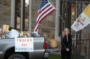 A woman collects toy trucks at the funeral of 2-year-old Maddox Derkosh at Saint Bernard Church in Mount Lebanon, Pa., on Friday.