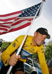 In this July 24, 2005 file photo, Lance Armstrong carries the United States flag during a victory parade on the Champs Elysees in Paris after winning his seventh straight Tour de France.