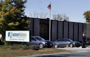 Two men stand guard outside the entrance to Ameridose LLC in Westborough, Mass.