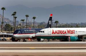 America West and US Airways jets taxi along runway two at Sky Harbor International Airport Sunday in Phoenix in this Sept. 4, 2005 file photo.