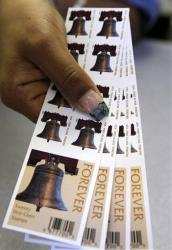 In this 2009 file photo, a US Postal Service employee displays Forever stamps.
