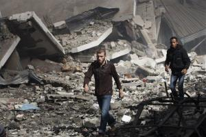 Palestinians walk through the debris after an Israeli air strike on building in Gaza City, Sunday, Nov. 18, 2012.