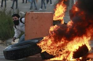 A Palestinian man hides during a protest against Israel's operations in Gaza Strip, outside Ofer, an Israeli military prison near the West Bank city of Ramallah, Sunday, Nov. 18, 2012.