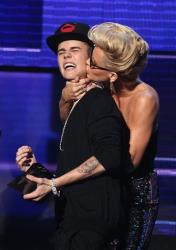 Justin Bieber is smothered in kisses by presenter Jenny McCarthy as he accepts an award at the 40th Anniversary American Music Awards on Sunday, Nov. 18, 2012, in Los Angeles.