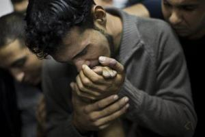 A Palestinian man kisses the hand of a dead relative in the morgue of Shifa Hospital in Gaza City, Sunday, Nov. 18, 2012.