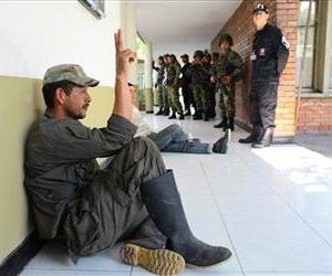A rebel of the Revolutionary Armed Forces of Colombia, or FARC, signals a victory sign after being captured by army, along with one other rebel, in Neiva, Colombia, Oct. 10, 2012.
