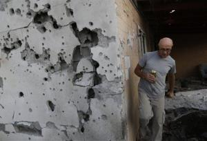 A resident walks outside a damaged house after a rocket fired by Palestinian militants from inside the Gaza Strip, landed at the community of Ofakim, in southern Israel, Sunday, Nov. 18, 2012.