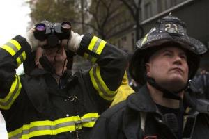 FDNY firefighters glare up at a damaged crane as it hangs over 57th Street after being torn from it's base by high winds, Monday, Oct. 29, 2012, in New York.