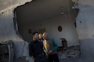 Palestinians gather near a destroyed building after an Israeli strike in Beit Lahia, north Gaza today.