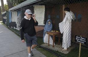 In this Dec. 13, 2011 file photo, a man walks past two of the traditional Nativity scenes along Ocean Avenue at Palisades Park in Santa Monica, Calif.