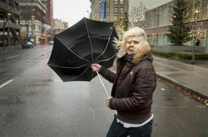 During a strong gust of wind, Michele Purkey's umbrella flips back as she crosses the intersection of First Avenue and Wall Street on Nov. 19, 2012, in downtown Spokane, Wash.
