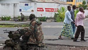 People walk past as M23 rebel soldiers take positions near the Heal Africa hospital in the center of  Goma, Congo yesterday.