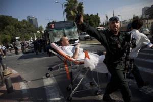 Israeli rescue workers and paramedics carry a wounded person from the site of a bombing in Tel Aviv, Israel, Wednesday, Nov. 21, 2012.