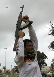 An anti-Libyan leader Moammar Gadhafi gunman holds up his AK-47 as he fires in the air to celebrate the freedom of the Libyan city of Benghazi, Libya.