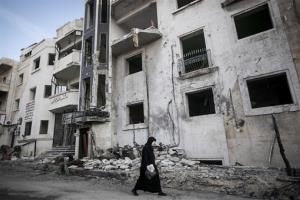 In this Saturday, Nov. 17, 2012 photo, a Syrian woman walks in front of a destroyed hospital where heavy clashes took place between rebel fighters and the Syrian army.
