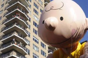 The Charlie Brown balloon passes people on balconies on New York's Central Park West during the 86th annual Macy's Thanksgiving Day Parade,Thursday, Nov 22, 2012.