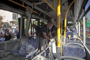 Israeli police officers examine a destroyed bus at the site of a bombing in Tel Aviv, Israel, Wednesday, Nov. 21, 2012.