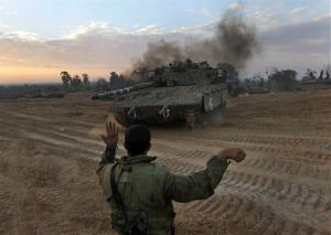 An Israeli soldier guides a tank to a new position at a staging area near the Israel Gaza Strip Border, southern Israel, Thursday, Nov. 22, 2012.