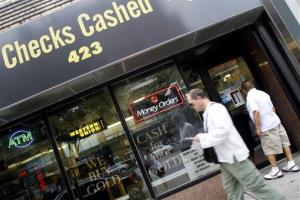 In this Aug. 10 2010, a man looks into the UBNY check cashing store as another walks past, in the Hell's Kitchen neighborhood of Manhattan in New York.