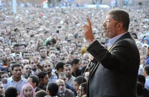 In this Friday, Nov. 23, 2012, photo released by the Egyptian Presidency, President Mohammed Morsi speaks to supporters outside the Presidential palace in Cairo, Egypt.