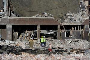 Inspectors stand in debris, Saturday, Nov. 24, 2012, at the site of a gas explosion that leveled a strip club in Springfield, Mass., on Friday evening.