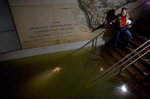 In this Wednesday, Oct. 31, 2012 file photo, MTA Vice President Joseph Leader shines a flashlight on standing water in a train station in New York in the wake of Superstorm Sandy.